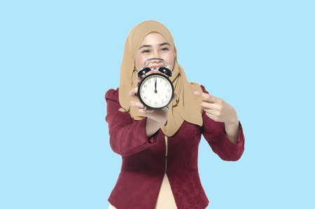time management and punctuality at work concept, beautiful hijab women holding vintage alarm clock