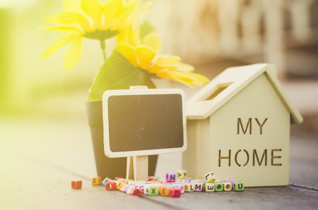 miniature wooden house with signage for real estate and mortgage concept Stock Photo