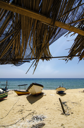 Beautiful scenery under bamboo hut, traditional fisherman boat stranded on deserted sandy beach under bright sunny day.
