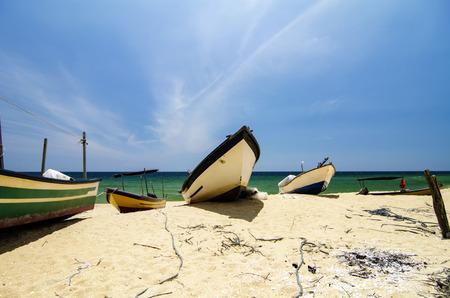 Beautiful scenery, traditional fisherman boat stranded on deserted sandy beach under bright sunny day.