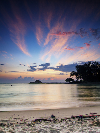 beautiful tropical beach with silhouette of tree over sunrise background. clouds and sunlight on horizon Stock Photo