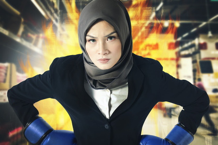 Creative ideas concept, successful and aggressive young muslimah businesswomen with boxing glove over abstract double exposure background