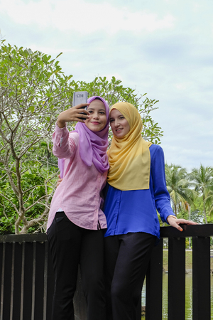 Happy beautiful muslimah having fun, spend time together and selfie at the city park