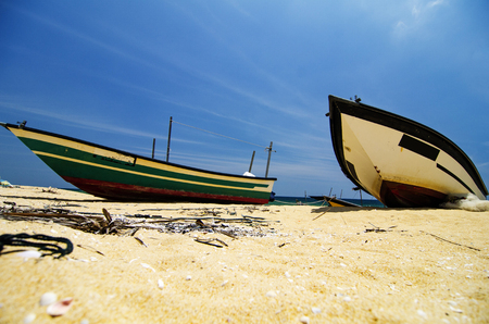 Beauty in nature,fisherman boat stranded on deserted sandy beach under bright sunny day. Stock Photo