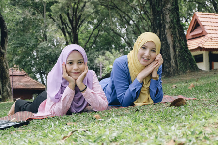 Outdoor lifestyle, friendship and happiness concept. portrait of smile young muslimah laying on grass at city park