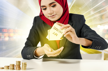 Creative ideas concept, successful young muslimah  saving money for her dream house over abstract double exposure background