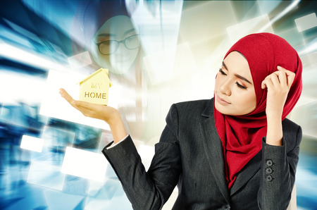 Creative ideas concept, successful young muslimah businesswomen dream to own house over abstract double exposure background Stock Photo