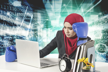 stress young businesswomen with boxing glove look at her laptop.cyber security business concept with abstract double exposure Stock Photo