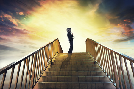 Creative ideas and stairs to success concept , young professional holding book and look at abstract background to expressing her future Stock Photo