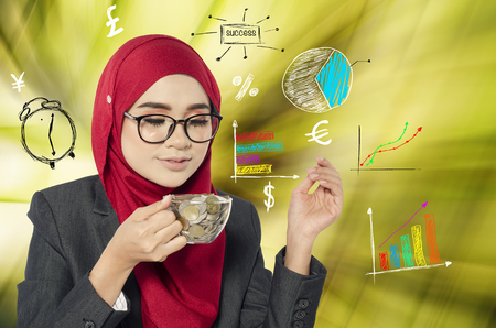 financial concept, successful young muslimah businesswomen holding cup of coins over abstract double exposure  background Stock Photo