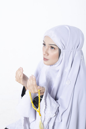 young woman wear shawls for prayer and hand holding beads Stock Photo