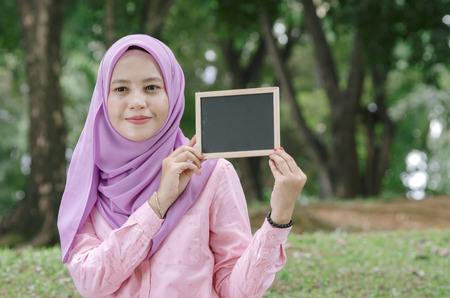 portrait of pretty young excited woman holding empty blank chalkboard for text. Stock Photo