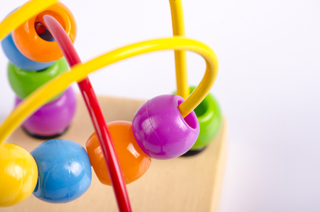 childhood, beads, toys, white, background, toddler, wood, game, spiral, loop, ball, puzzle, skills, baby, colorful, green, purple, reflection, ideas, creative, concept, macro, learning, abacus Stock Photo