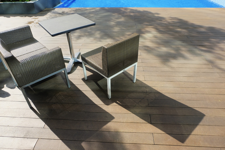 chairs and table side near the pool ideal for travel and vacation concept.bright sunny day and shadow on wooden platform