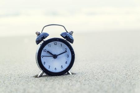 vintage alarm clock on sandy beach. selective focus and grain effect