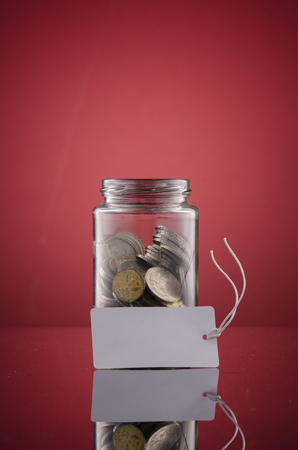 coin in transparent glass jar over red background for financial concept