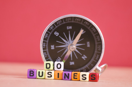 DO BUSINESS word cube and compass for business direction concept Stock Photo