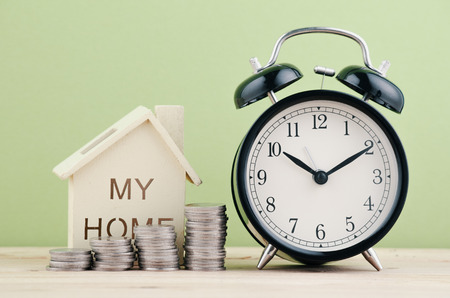 Taking time saving for dream house concept, stacking coins and alarm clock on wooden desk