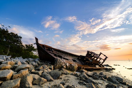 blurred and selective focus silhouette image of abandon shipwrecked on rocky shoreline. dark cloud and soft on water
