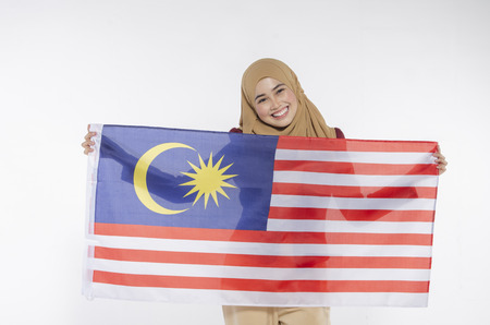 young malaysian civilian with happy face celebrating independent day. hand holding flag