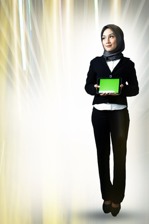 Portrait of beautiful young lady standing and holding tablet against double exposure background