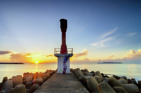 Beauty in nature, morning scenery of abandon becon tower and groyne structure at sunrise background.