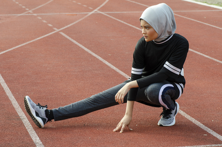 Sport and healthy lifestyle concept. young athlete with hijab stretching and warming up before running