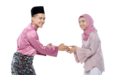 Portrait of young man with traditional clothing shaking hand his wife during hari raya over white background Imagens