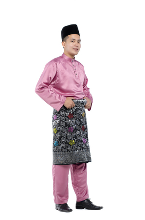 年轻和英俊的亚裔人画象有传统衣物的在hari raya在白色背景的