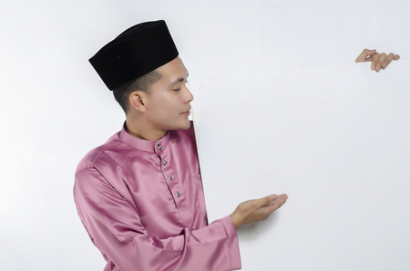 Portrait of young and handsome asian man with traditional clothing holding white cardboard Stock Photo