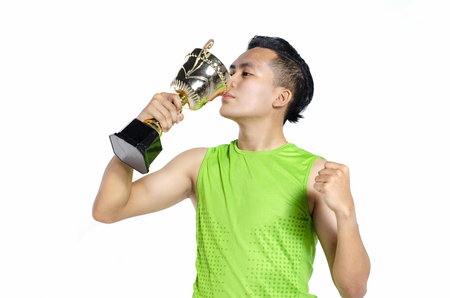 Happy expression young fit man in sportswear, holding and kissing gold trophy over white background