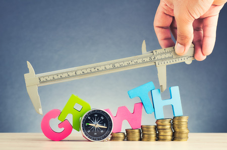 Business success concept, stacking coins and word GROWTH on wooden desk over beautiful reverberation gradient background