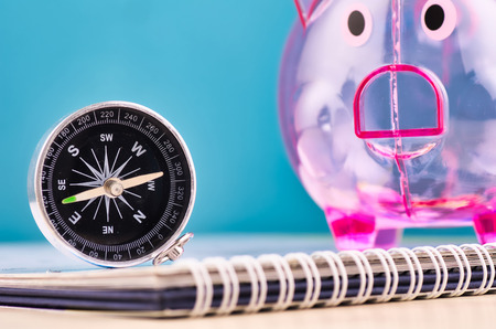 compass on calendar over piggy bank background for future financial direction planning concept