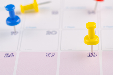 close up of colorful pin on calendar for business appointment or planning concept