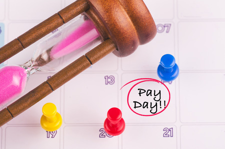 Payroll or accounting concept,hourglass, thumbtack and word PAY DAY for remind on calendar