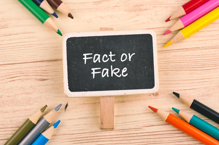 FACT OR FAKE word on signage pointing by color pencil over wooden background 免版税图像