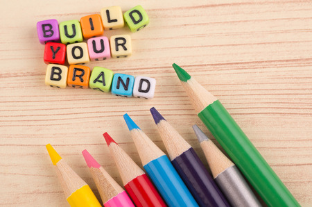 Colorful cube word BUILD YOUR BRAND on wooden background for advertising and commercial marketing concept