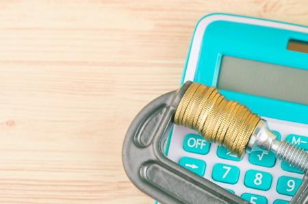 Abwertung und Finanzkrise, Taschenrechner und Münzen fest in einer G-Klemme gequetscht Standard-Bild