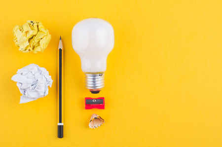 pencil, crumple paper and bulb over yellow background for creative ideas concept