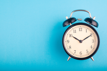 Time management concept, alarm clock on blue background. copy space for text