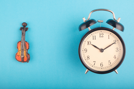 Time management concept, alarm clock and violin on blue background. copy space for text