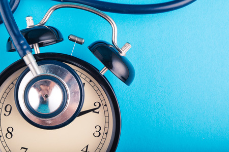 health and medical concept, alarm clock and stethoscope on blue background. copy space for text