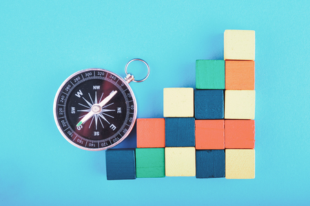 compass and colorful wooden cube on blue background for travel or direction concept