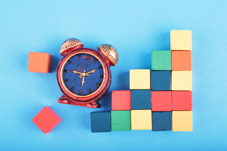 Time management concept, miniature alarm clock and wooden cube on blue background.