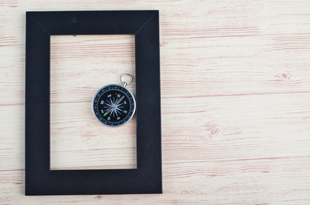 top view empty photo frame and compass on wooden background