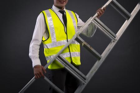young technician or engineer holding alumminium ladder over dark background Reklamní fotografie