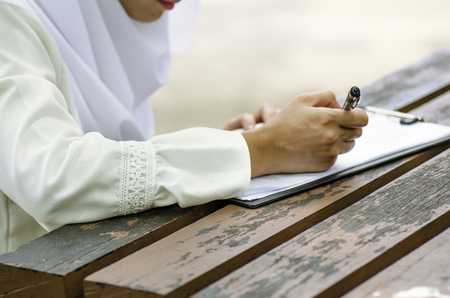 close up image of young woman signing form, sitting on wooden table