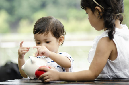 Learning financial and planning savings concept, young kids putting coins into piggy bank 版權商用圖片