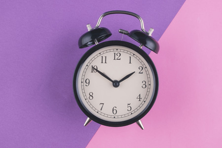 Time management concept, alarm clock on purple background. copy space for text
