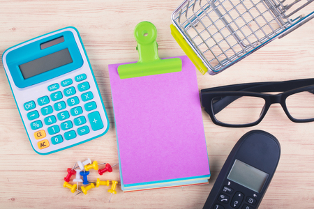 Financial or budget planning concept background,top view of notepad mobile phone, calculator, and other accessories on wooden desk